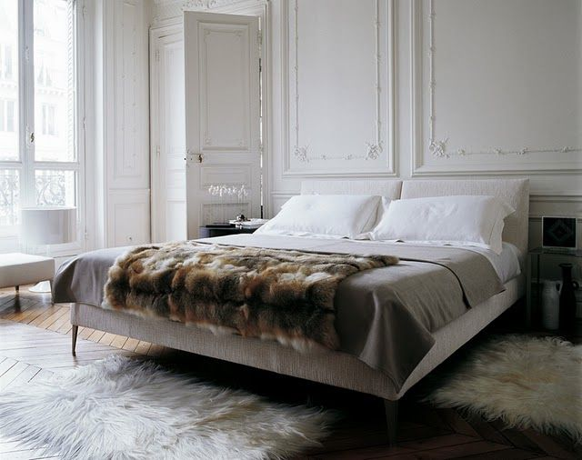 This is the 'Bedroom Of My Dreams' - fur, parquetry, high ceiling, wall panels, white line bed, stark white walls, big french doors and and it's probably in Paris - freakin' amazing.