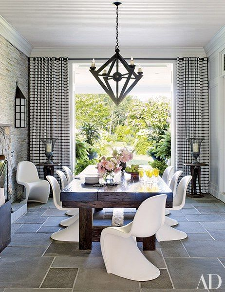 Verner Panton chairs by Vitra join a chandelier by Jerry Pair on an enclosed porch.