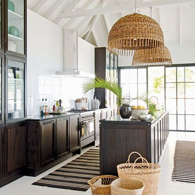 British Colonial elements in this kitchen, like the high ceilings & tall glass china cupboard & rattan pendant shades give this room an tropical feel.