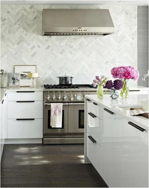 herringbone marble tile with gloss white cabinets, white countertops and dark stained wood floors