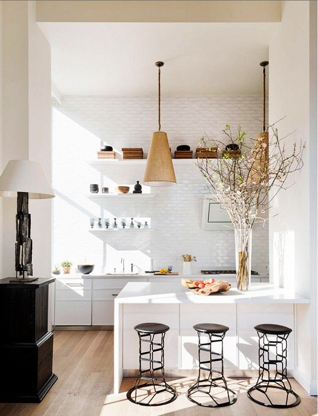 White kitchen with sculptural stools and high ceilings