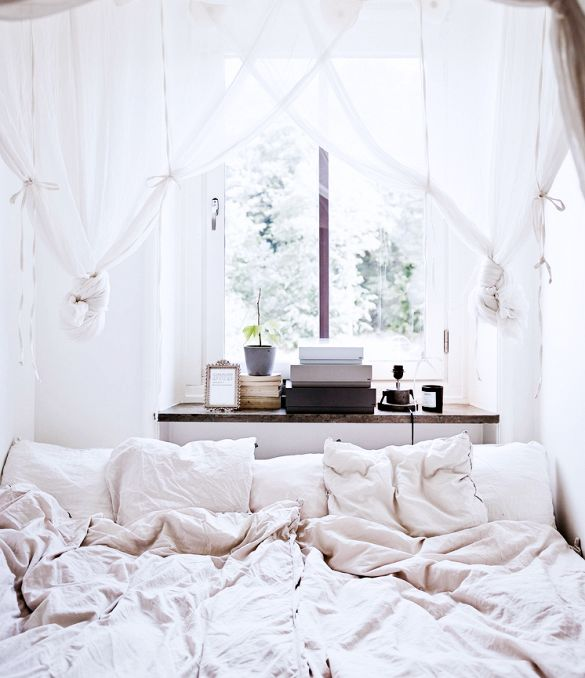 Inside a Chic Small Home With Major Style | DomaineHome.com // Cozy sleeping space with linen bedding and gauzy canopy.