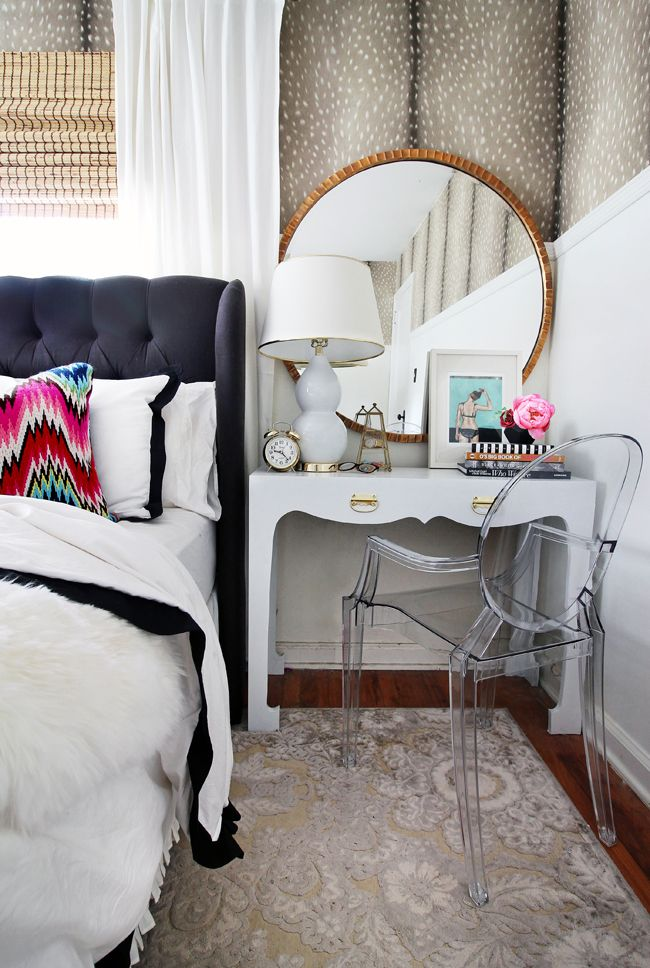 Desk/vanity as nightstand with gorgeous black tufted wingback headboard, round mirror and ghost chair