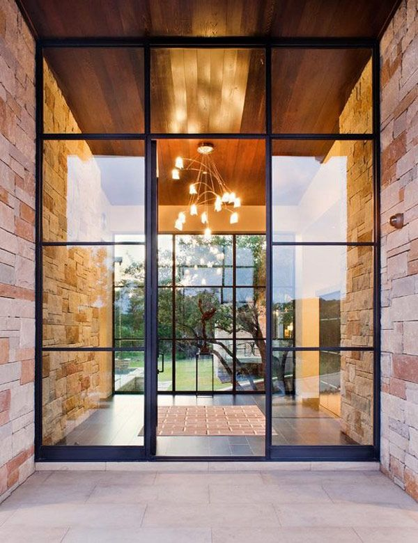 the glass entrance of this Texas home frames a naturally inspired, clean entryway featuring a contemporary chandelier.