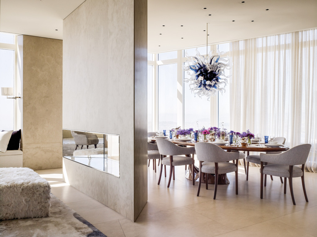 In the dining room, a Dale Chihuly sculpture hangs above the custom-carved walnut dining table. Classic 1959 dining chairs by Ole Wanscher are upholstered in textured Calvin Fabrics. At left is the living room. The floor is Flavigny limestone.
