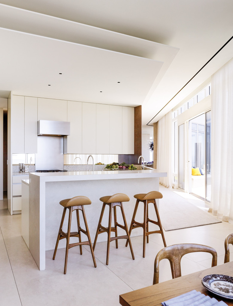In the low-key kitchen, midcentury teak barstools with rosewood footrests are by Erik Buch. I