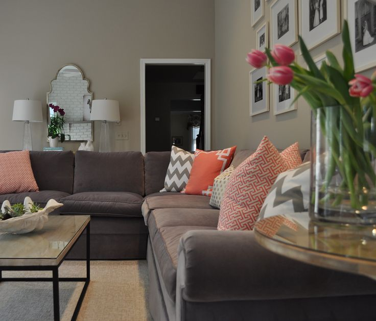 Gorgeous coral, gray and white family room. Gray sectional sofa, natural decor; Caitlin Wilson pillows, morrocan mirror, wall gallery     JWS Interiors  www.jws-interiors.com