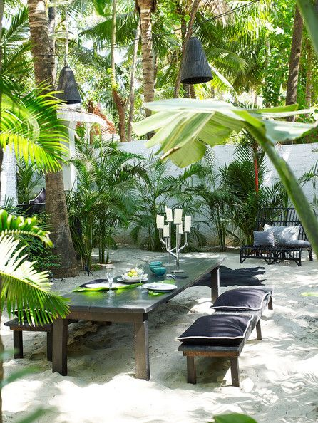 Garden - A tropical outdoor dining space on the sand with hanging lanterns. @lonnymag
