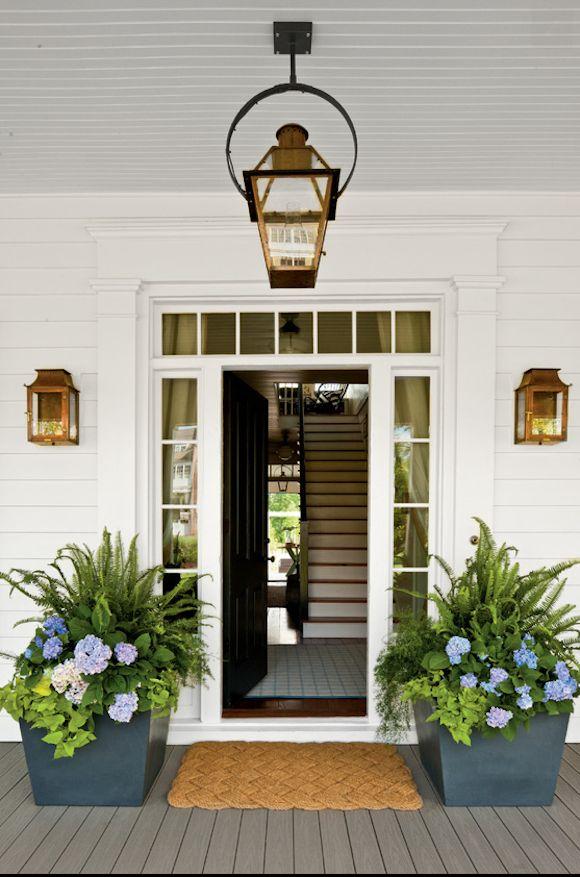 So inviting, clean and crisp white front porch with lanterns, and painted gray porch floor.