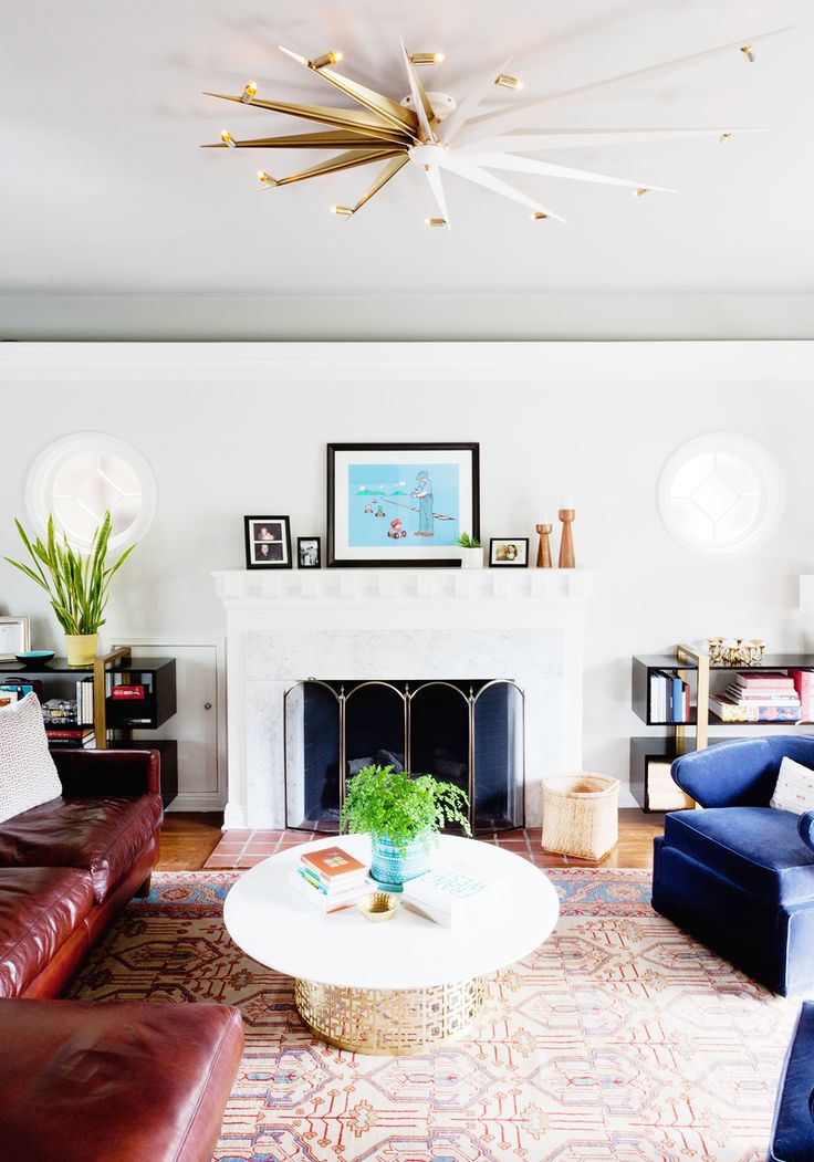An elegant and colorful living room space with leaning art on fireplace mantle, blue chairs, and gold light fixture: