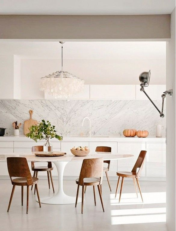 Bright, white kitchen with rustic dining space: