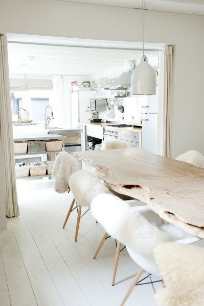 All white kitchen and dining. The sheepskin chair covers are a warm and inviting decor idea. Home Decor Salle à manger: