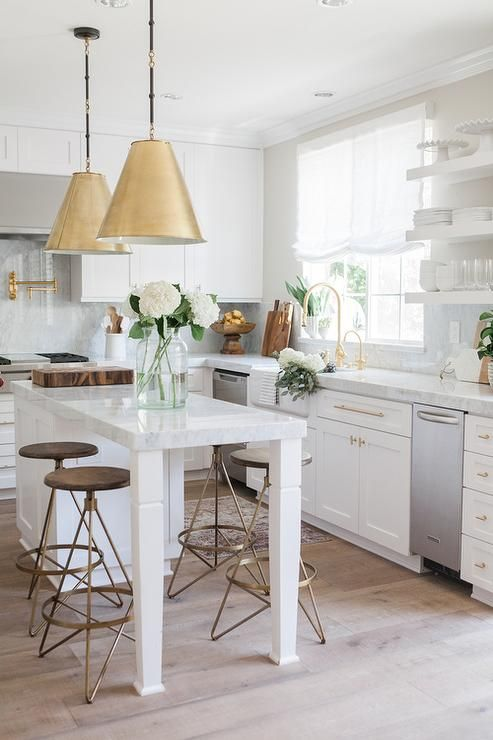 Two Goodman Hanging Lamps in Antique Brass stands over a white kitchen island topped with gray and white quartzite lined with round brass and wood counter stools, Arteriors Wyndham Swivel Counter Stools.: