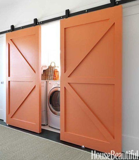 12 Ways to Incorporate Barn Doors in Your Home: Coral paint gives these barn doors a modern twist — a stylish way to conceal a laundry nook while introducing color to a room.   Source:
