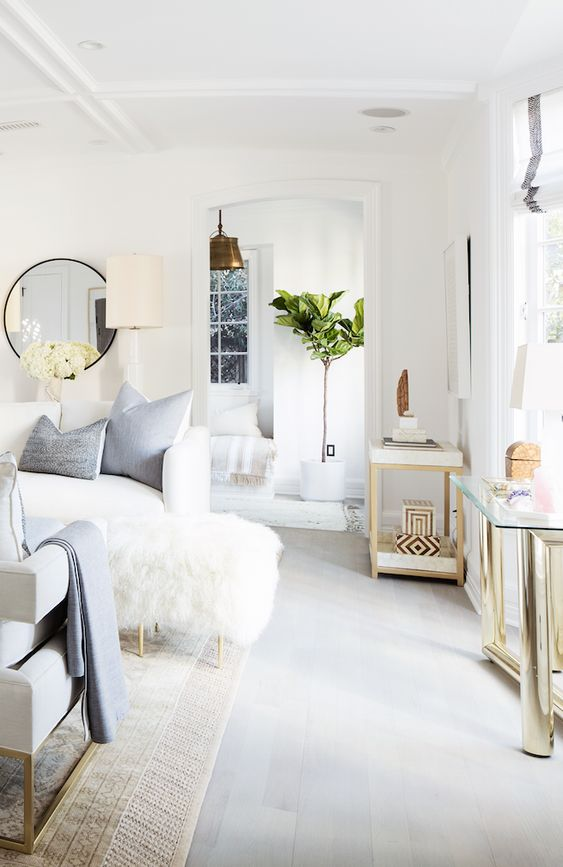 All-white living room with blonde wood and brass layered in.: